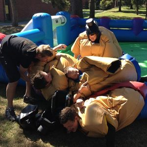 sumofotboll killar bygger hög med sumodräkter